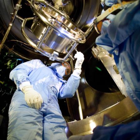 Due operatori in tuta bianca lavorano sullo specchio dell'esperimento Virgo